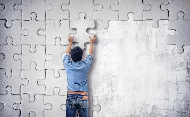 Homem fazendo um quebra-cabeça na parede. parede vazia com espaço para texto