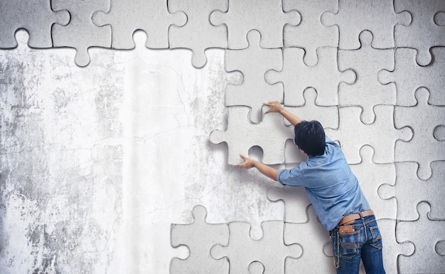 Homem fazendo um quebra-cabeça na parede.