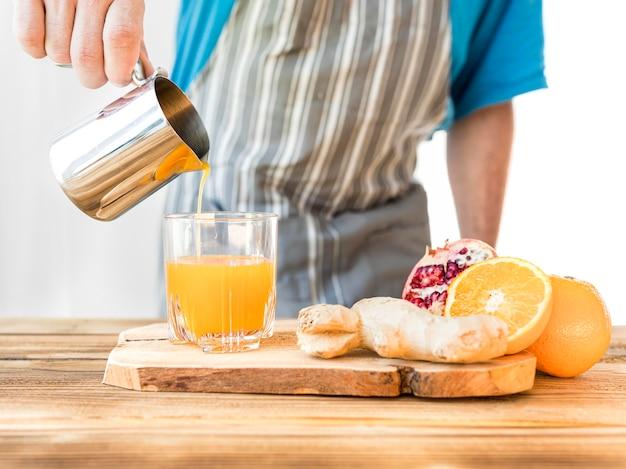 Homem fazendo um suco de laranja