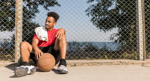 Homem fazendo uma pausa após um jogo de basquete com espaço de cópia