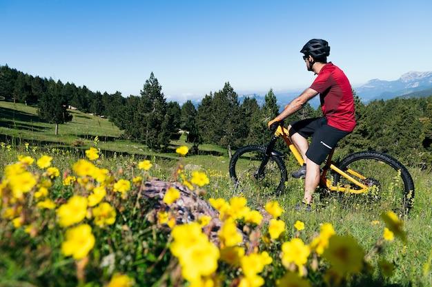 Homem fazendo uma pausa em sua mountain bike em um prado