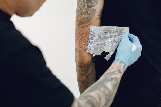 Homem fazendo uma tatuagem em um salão de tatuagem