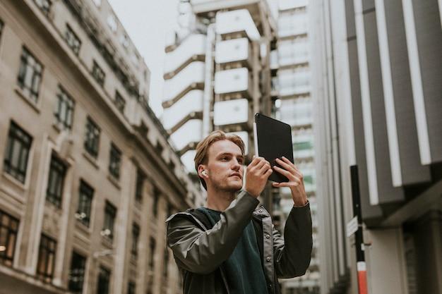 Homem fazendo uma videochamada em seu tablet digital em uma cidade