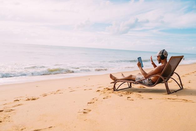 Homem fazendo uma videochamada nas férias de verão