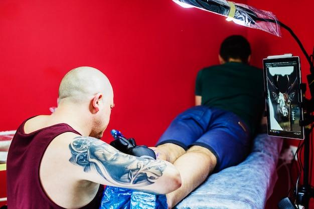 Homem, fazer, tatuagem, ligado, perna, em, estúdio