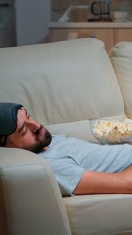 Homem fechando os olhos e adormecendo no sofá da sala em frente à tv, enquanto o entretenimento da televisão está ligado
