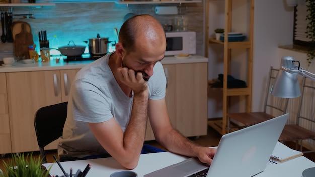 Homem fechando os olhos enquanto trabalhava na cozinha de casa durante um prazo final à noite. ocupado e exausto funcionário remoto cochilando na cadeira, acordando trabalhando no laptop, usando tecnologia moderna, fazendo horas extras.