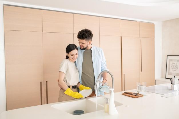 Homem feliz abraçando sua esposa lavando pratos depois do café da manhã