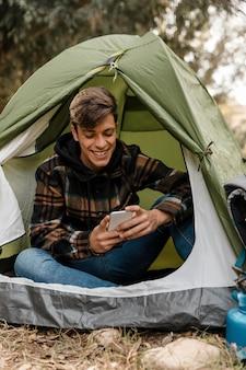Homem feliz acampando na floresta usando telefone celular