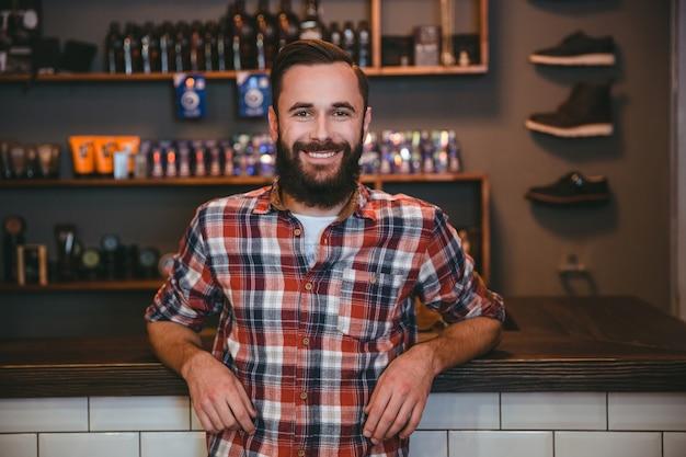 Homem feliz, alegre e satisfeito com barba em uma camisa xadrez na barbearia depois de visitar o barbeiro