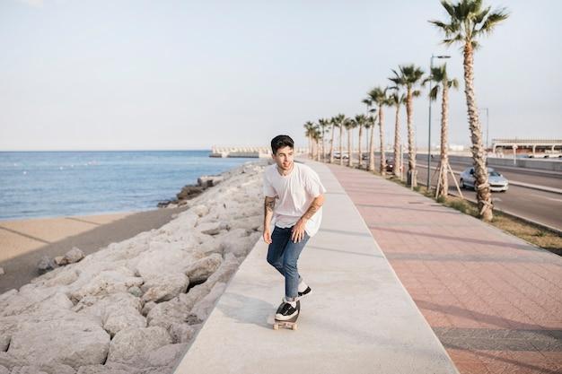 Homem feliz andando de skate perto da costa