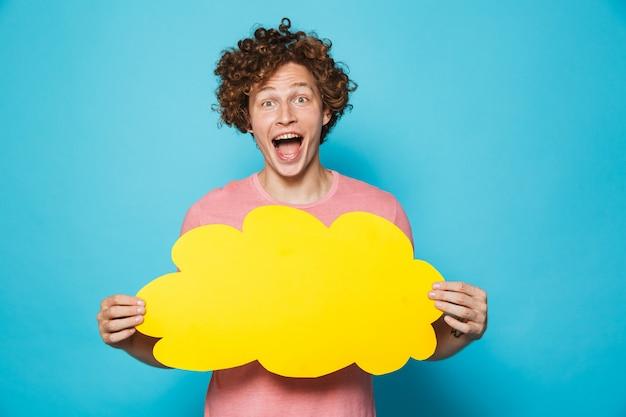 Homem feliz animado com cabelo castanho encaracolado, gritando e segurando a bolha amarela