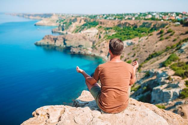 Homem feliz ao ar livre na beira de um penhasco, apreciando a vista na rocha do topo da montanha