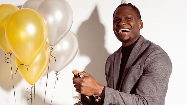 Homem feliz ao lado de balões