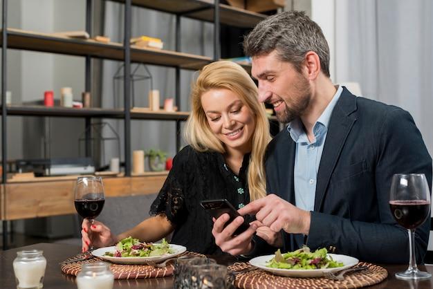 Homem feliz apontando no smartphone para mulher alegre na mesa