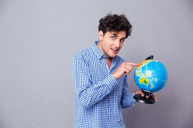 Homem feliz apontando o dedo no globo