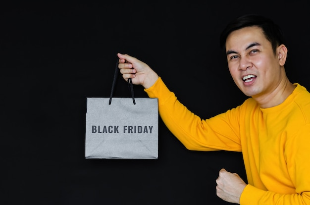 Homem feliz asiático segurando a sacola de compras em fundo escuro para o conceito de sexta-feira negra.