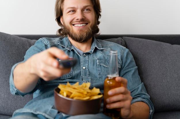 Homem feliz assistindo tv em casa