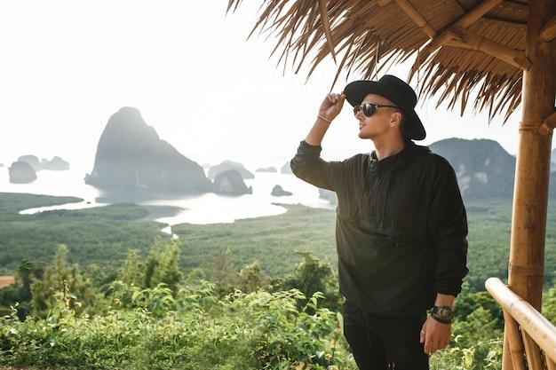 Homem feliz atraente na natureza de chapéu e casaco preto com montanhas, jovem viajante com relógio de mão de luxo, cara rico em pé perto de bangalô no ocaso