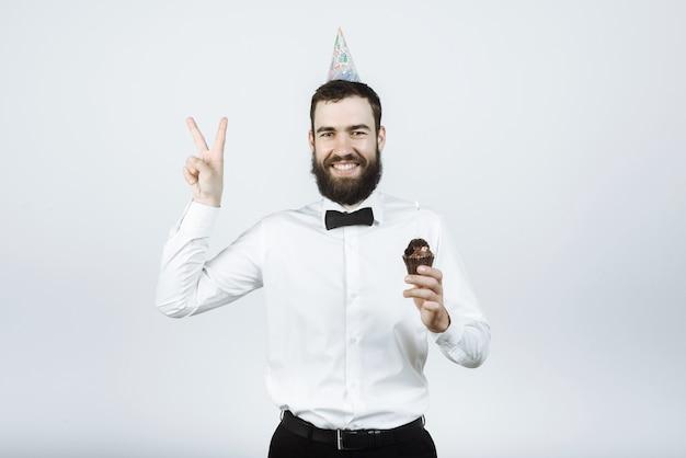Homem feliz barbudo hippie com boné de camisa e gravata borboleta segurando bolo e mostrando pis no estúdio em cinza