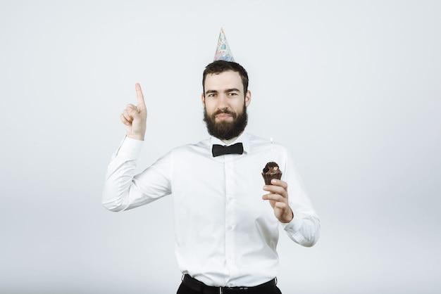 Homem feliz barbudo hippie com boné de camisa e gravata borboleta segurando um bolo no fundo cinza isolado