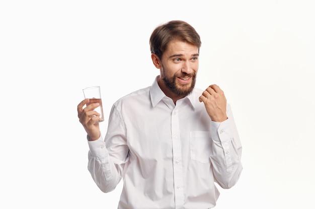 Homem feliz bebe água de um copo em um modelo de retrato de camisa branca clara.
