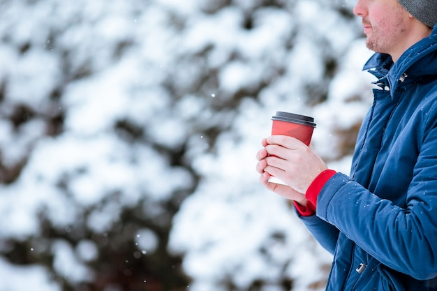 Homem feliz bebendo café ao ar livre no inverno