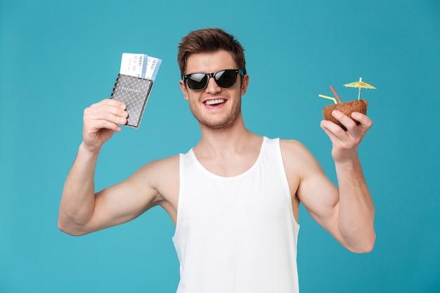 Homem feliz bebendo cocktails com bilhetes.
