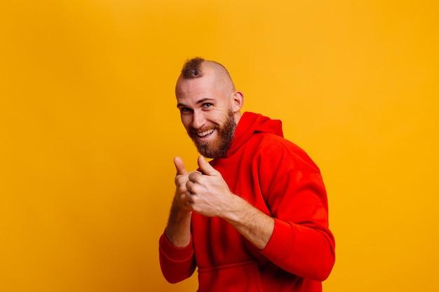 Homem feliz bonito e brutal com um casaco de lã da moda de inverno vermelho quente