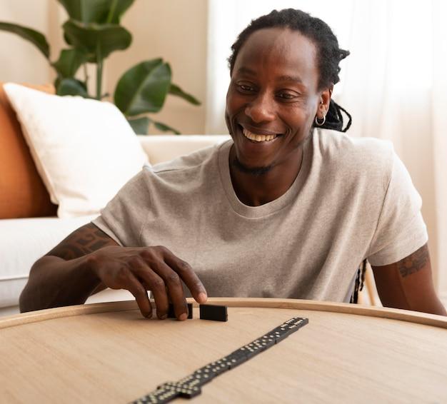 Homem feliz brincando com peças de dominó