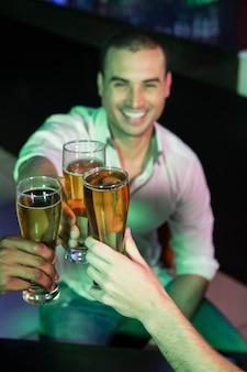 Homem feliz, brindando seu copo de cerveja com os amigos no bar