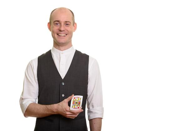 Homem feliz, careca, mágico, caucasiano, sorrindo e dobrando o cartão do valete de ouros