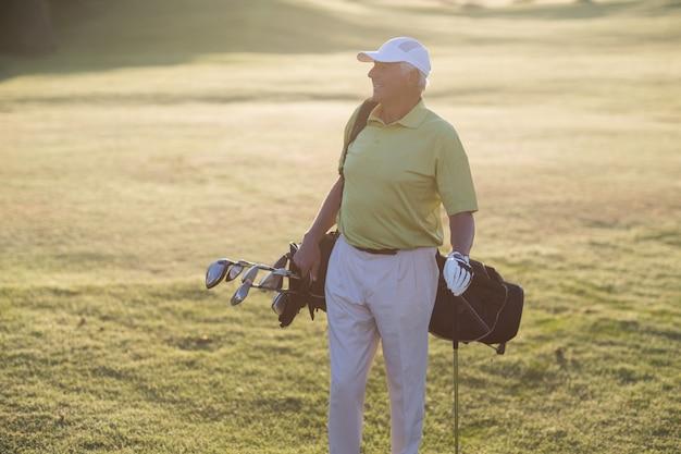 Homem feliz, carregando o saco de golfe
