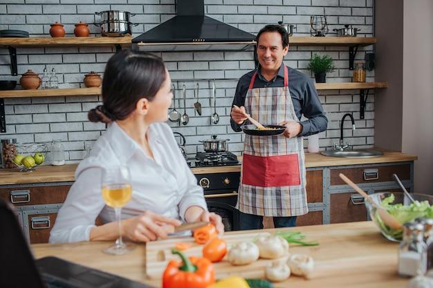 Homem feliz carrinho no fogão na cozinha.