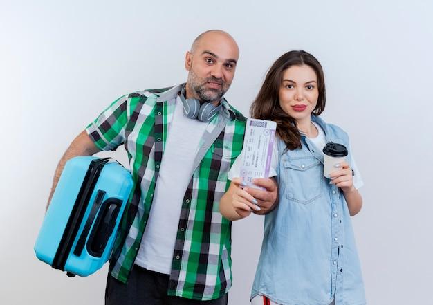 Homem feliz casal viajante adulto usando fones de ouvido no pescoço, segurando uma mala, mulher segurando uma xícara de café de plástico, ambos segurando o bilhete olhando