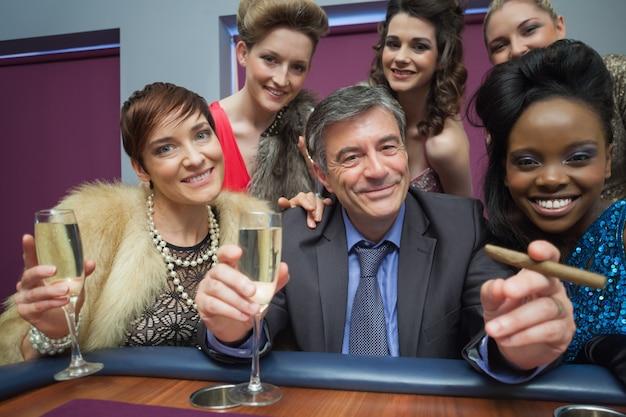 Homem feliz cercado por mulheres na mesa de roleta