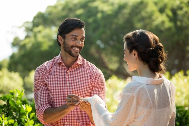Homem feliz colocando um anel de noivado em uma mulher no parque