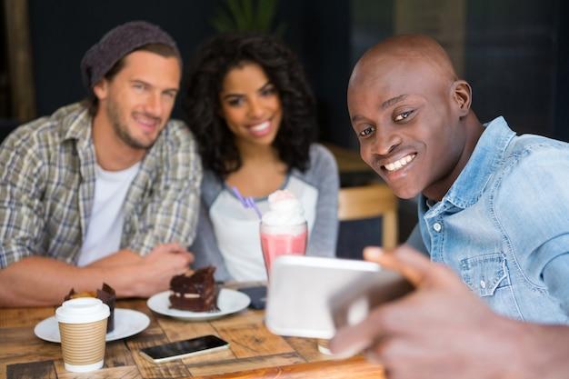 Homem feliz com amigos tirando selfie em uma mesa de madeira em uma cafeteria