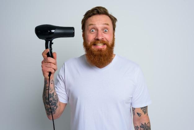 Homem feliz com barba brincando com secadores de cabelo e uma arma de fogo