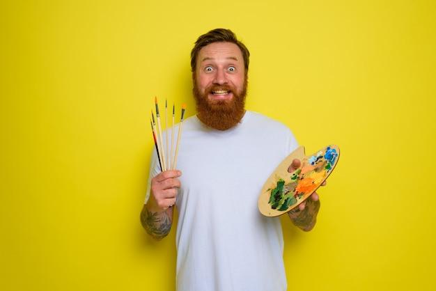 Homem feliz com barba e tatuagem pronto para desenhar com pincéis