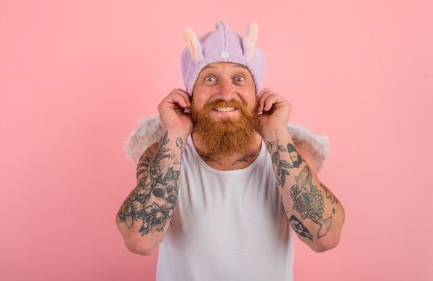 Homem feliz com barba e tatuagens age como um anjo