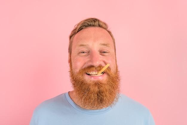 Homem feliz com barba e tatuagens comendo batatas fritas