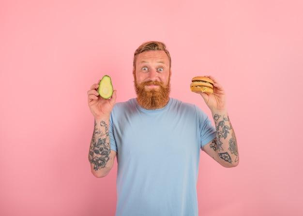 Homem feliz com barba e tatuagens está indeciso se comer um abacate ou um hambúrguer