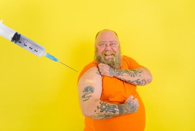 Homem feliz com barba e tatuagens faz a vacina contra o vírus covid-19