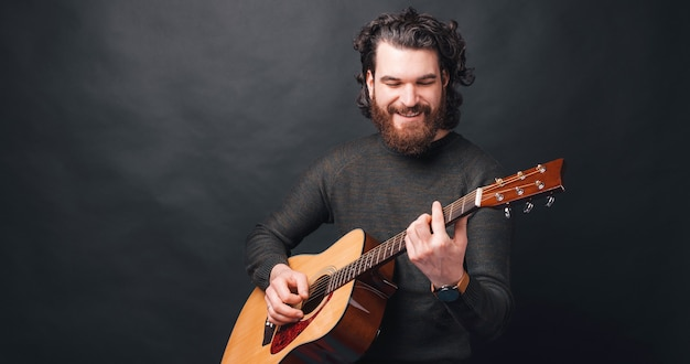 Homem feliz com barba tocando violão no escuro e sorrindo