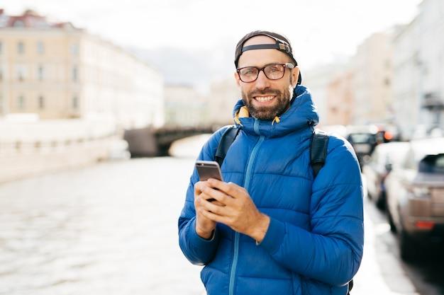 Homem feliz com barba, usando óculos, vestido de anoraque azul, segurando a mochila e móvel tendo olhar feliz, viajando na cidade