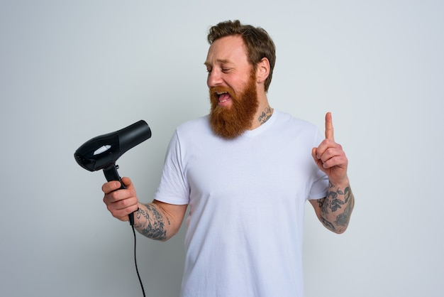 Homem feliz com barba usando secador de cabelo como microfone e dança