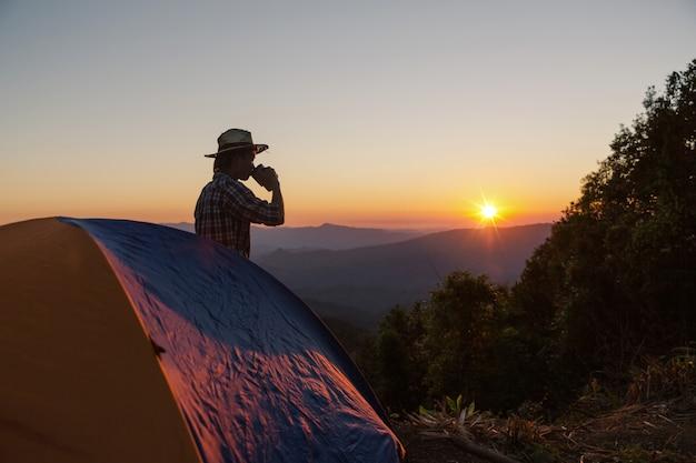 Homem feliz com bebida ficar perto da tenda ao redor de montanhas sob a luz do sol