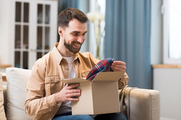 Homem feliz com caixa encomendada online