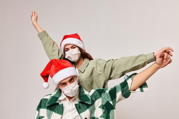 Homem feliz com camisa xadrez e mulher com chapéu festivo gesticulando